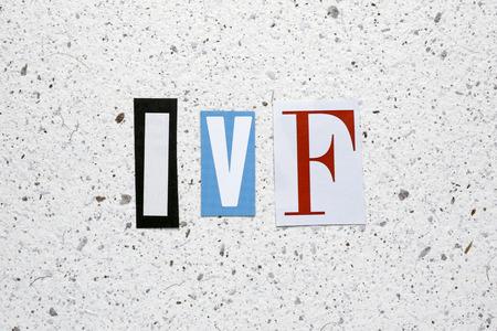 ivf: IVF (In Vitro Fertilization) acronym cut from newspaper white handmade paper texture