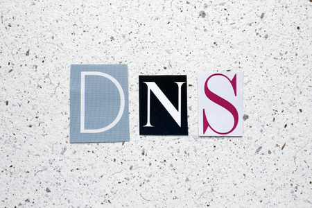 dns: DNS (Domain Name System) acronym cut from newspaper on white handmade paper texture Stock Photo