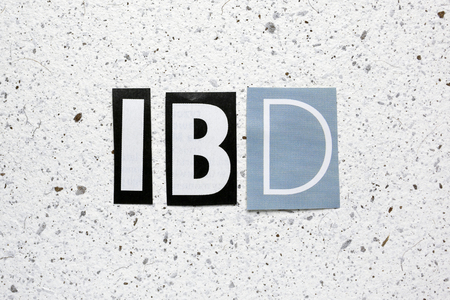 inflammatory bowel diseases: IBD (Inflammatory Bowel Disease) acronym cut from newspaper on white handmade paper texture Stock Photo