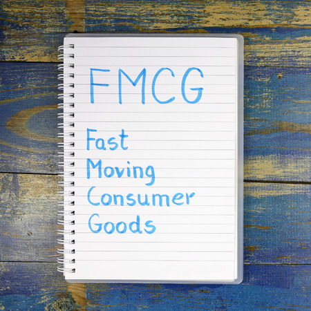 consumer goods: FMCG- Fast Moving Consumer Goods written in a notebook on wooden background