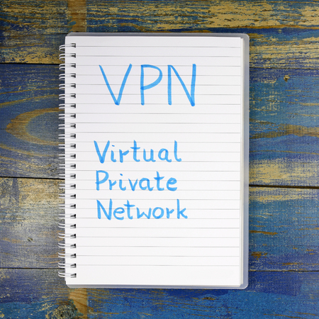 url virtual: VPN- Virtual Private Network written in a notebook on wooden background
