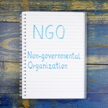 ngo: NGO- Non-Governmental Organization written in the notebook on wooden background