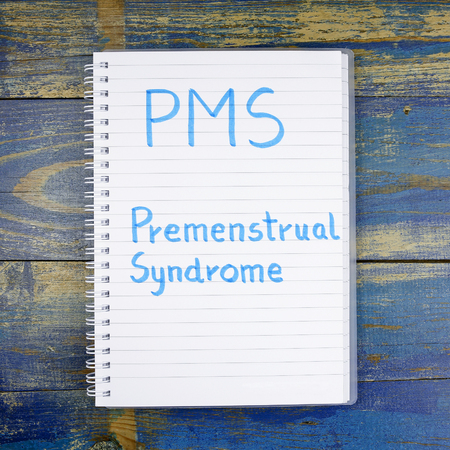 premenstrual syndrome: PMS- premenstrual syndrome written in a notebook on wooden background Stock Photo
