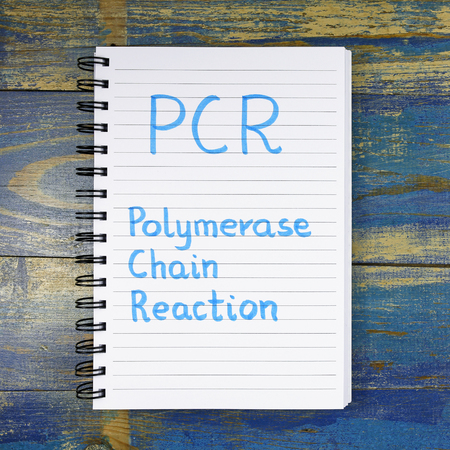 chain reaction: PCR-Polymerase Chain Reaction acronym written in a notebook on wooden background