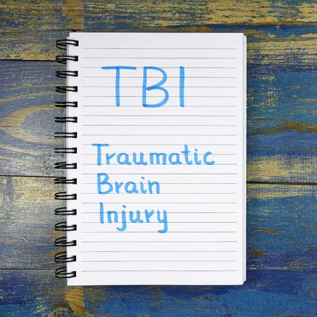 acronyme TBI- Traumatic Brain Injury écrit dans un cahier sur fond de bois
