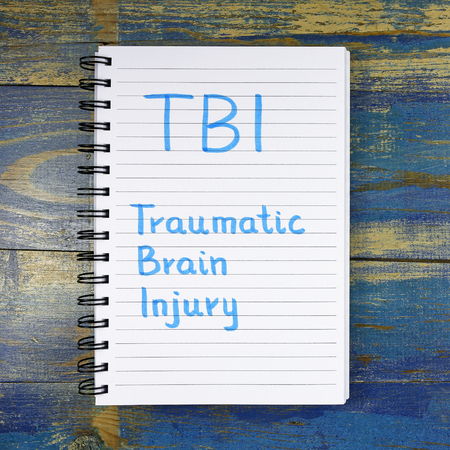 TBI- Traumatic Brain Injury acronym written in a notebook on wooden background