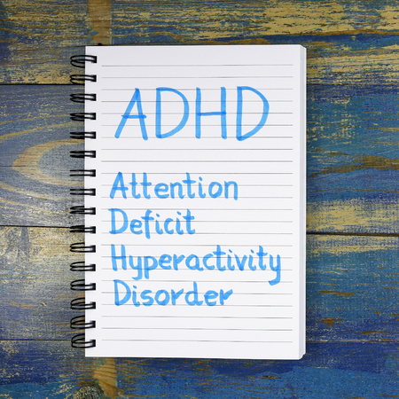 hyperactivity: ADHD- Attention Deficit Hyperactivity Disorder written in a notebook on wooden background Stock Photo