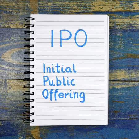 public offering: IPO- Initial Public Offering acronym written in a notebook on wooden background