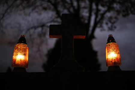kross stone and burning candles at the cemetery on All Saints Day Stock Photo