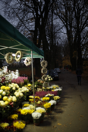 all saints day: stand with candles and chrysanthemums next to the cemetery on All Saints Day Stock Photo