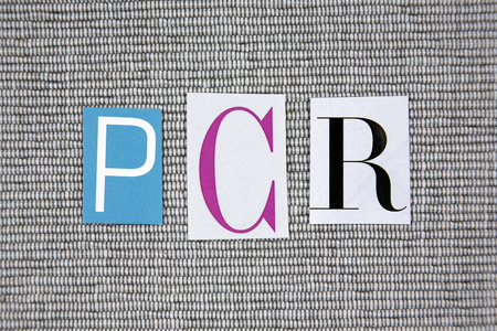 chain reaction: PCR (Polymerase Chain Reaction) acronym on gray background Stock Photo