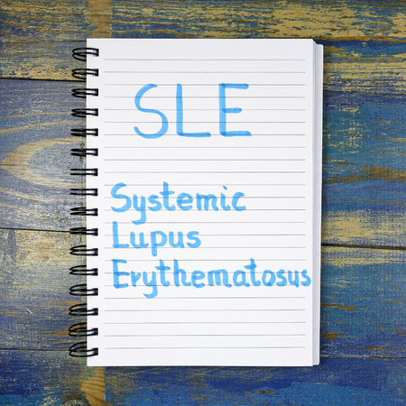 systemic: Tracking Systemic Lupus Erythematosus acronym written in a notebook on wooden background