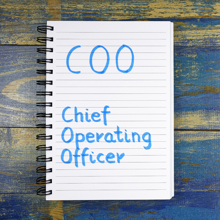 coo: COO Chief Operating Officer of text written in a notebook on wooden background
