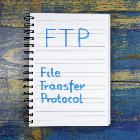 url virtual: FTP- File Transfer Protocol text written in a notebook on wooden background
