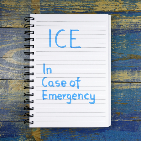 helthcare: ICE In Case of Emergency text written in a notebook on wooden background