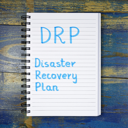 drp: DRP- Disaster Recovery Plan acronym written in a notebook on wooden background