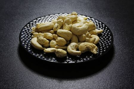 cashew nuts on plate on black background
