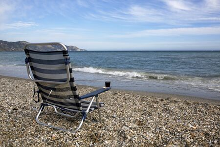 nerja: Empty sunbed with glass of red wine on the beach