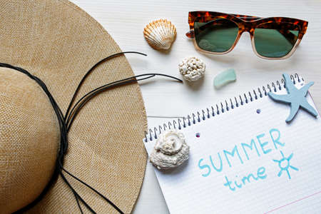 Straw hat, seashells, sunglasses and notebook on white background