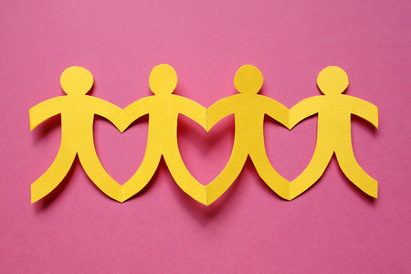Teamwork, yellow paper people on pink background