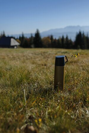 thermos on the mountain glade - concept of traveling