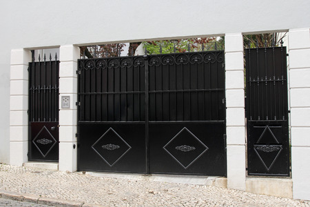 elegant, black entrance gate in white wall Stock Photo