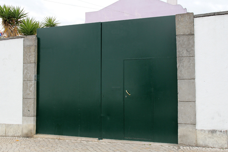 metal green gate in white wall