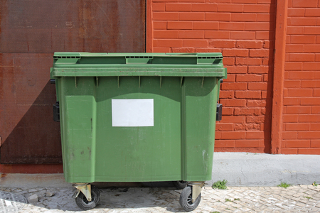 green garbage bin on the street Stock Photo