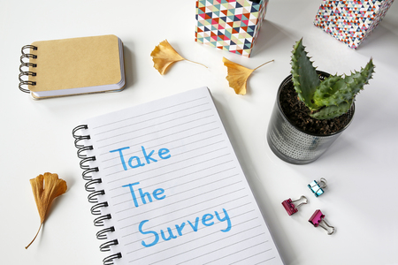 Take a survey written in notebook on white table