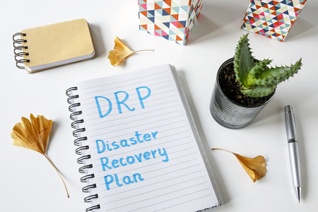 DRP Disaster Recovery Plan written in a notebook on a white table