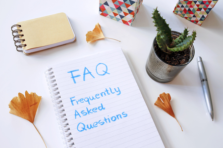 FAQ Frequently Asked Questions written in notebook on white table Banco de Imagens