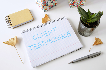 client testimonials written on a notebook on a white table Stockfoto
