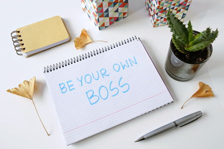 Be your own boss written in a notebook on a white table