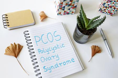 PCOS Polyzystisches Ovarialsyndrom in einem Notizbuch auf weißem Tisch geschrieben Standard-Bild