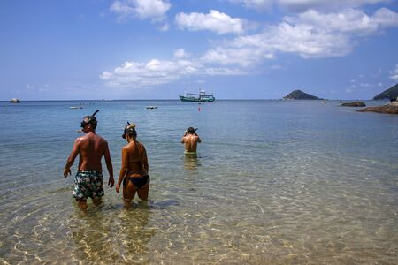 Koh Tao, Thailand - February 22, 2019: people in snorkeling masks in a crystal water of one of Koh Tao, very popular diving destination
