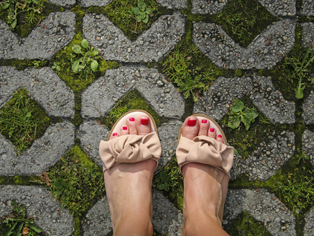 top view photo of woman feet in sandals on the stone pavement with grass