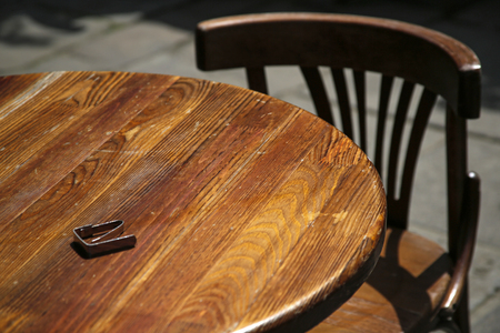 empty wooden chair and table in a street cafe