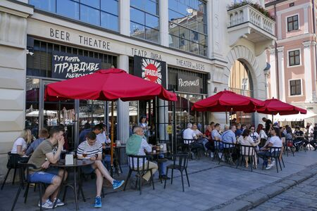 Lviv, Ukraine - june 1, 2019: tourists sitting outside The Pravda Beer Theatre. Its a very popular beer bar, tourist attraction.
