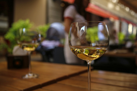 closeup of white wine glass at the table of street cafe 免版税图像