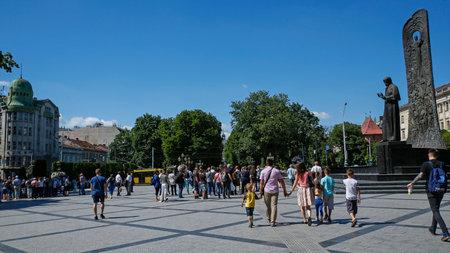 Lviv, Ukraine - june 1, 2019: turists walking next to the statue of Taras Shevchenko- famous ukrainian poet, artist located on prospect Svobody in Lviv