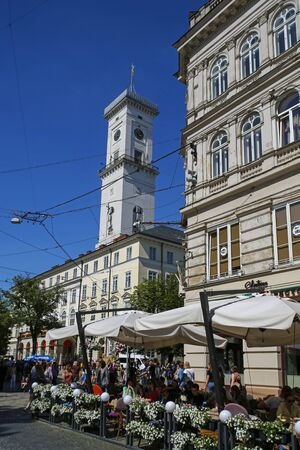 Lviv, Ukraine - june 1, 2019: people sitting in a restaurant and City Hall on Market Square in Lviv