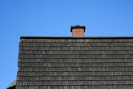 shingle roof and brick chimney against blue sky