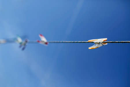 colorful clothespins on the rope against blue sky with selective focus
