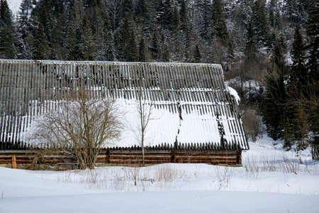 old abandoned wooden barn in winter scenery