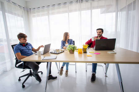 Business people working in office on desktop computer, Group of happy business people in smart casual wear looking at the laptop and gesturing. Achieving success. Stock Photo