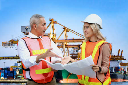 Female industrial engineer wearing a white helmet while standing in a construction site with businessman talking on working plan, Engineer and architects at construction site concept