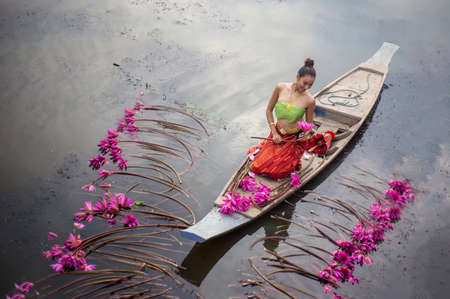 Young Asian women in Traditional dress in the boat and pink lotus flowers in the pond.Beautiful girls in traditional costume.Thai girl in traditional Thai northern traditional costume in lotus pond. Stock Photo