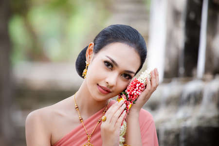 Beautiful Thai girl in Thai traditional costume. Asia woman wearing traditional Thai dress,The costume of the national dress of ancient Thailand against temple.