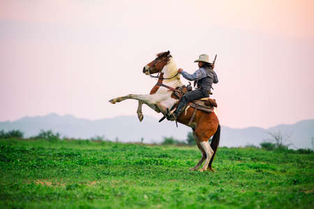 Cowboy riding a horse carrying a gun in sunset with mountain, Western cowboy portrait