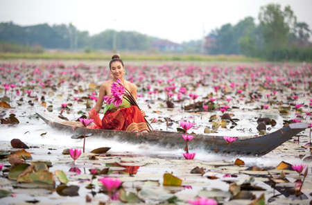Young Asian women in Traditional dress in the boat and pink lotus flowers in the pond.Beautiful girls in traditional costume.Thai girl in traditional Thai northern traditional costume in lotus pond.